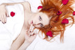 Beautiful red-haired girl in bed with rose petal.