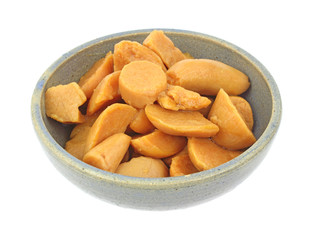 A large serving of cut canned yams in an old bowl