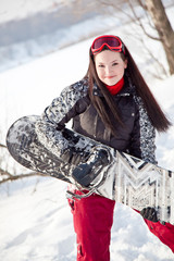 Joyful girl holds a snowboard
