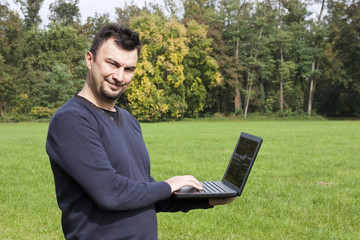 Young Adult Working in the Park with Laptop Computer