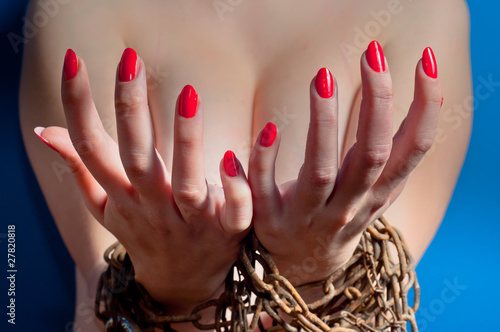 Red nails on girls hand on blue background