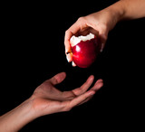 Woman hand giving an apple to man on black background
