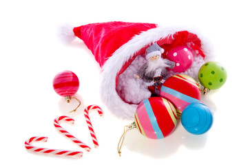christmas balls in the hat of santaclaus with candycane isolated