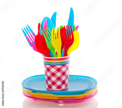 colorful plastic cutlery in a cup on plates  isolated over white