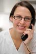 Zahnarzthelferin telefoniert mit einem Patienten