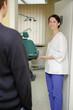 Zahnarzthelferin bittet Patient ins Behandlungszimmer