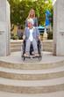 Seniorin im Rollstuhl vor Hindernis