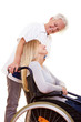 Krankenschwester redet mit Frau im Rollstuhl