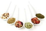 different spices and herbs in porcelain spoons