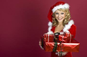 Frau in Santa Klaus Bekleidung mit Weihnachtsgeschenke.