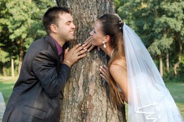 GROOM HOLDING BRIDE'S HAND BEHIND TREE