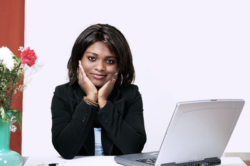 Pretty african woman at office desk with laptop