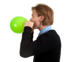 young man in black sweater inflating green balloon