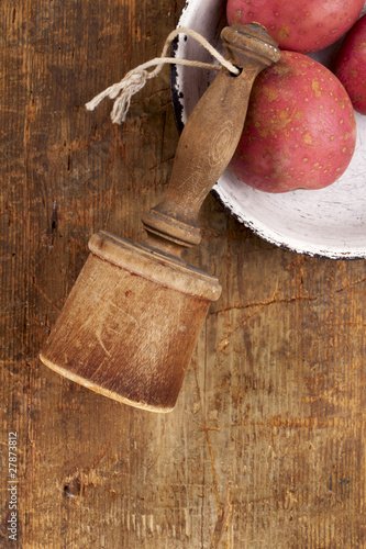 retro potato masher on old wooden table with potato