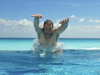 Sprung aus Swimmingpool mit Meerblick