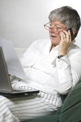 Women is working on laptop and calling by phone