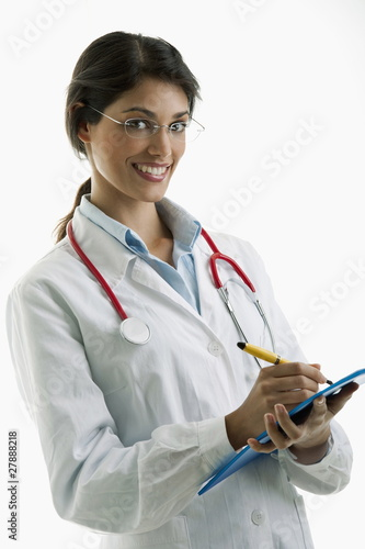 Doctor wearing stethoscope and writing on chart
