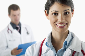 Doctor smiling and doctor reading medical chart