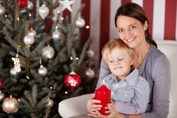 mutter und sohn mit kerze vor dem weihnachtsbaum