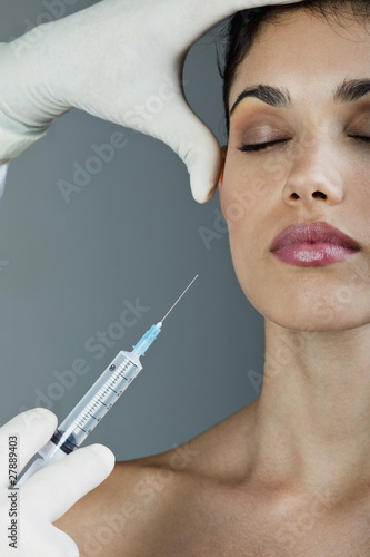 Hand holding botox syringe to young woman's face