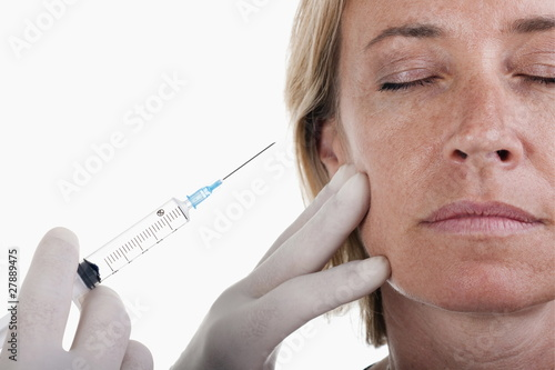 Hand holding botox syringe to woman's face