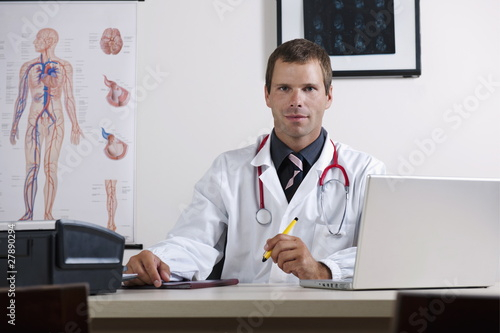 Doctor in his office with circulatory system chart and laptop