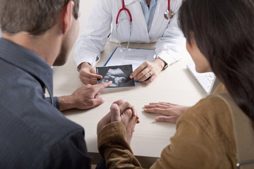 Doctor with ultrasound and couple