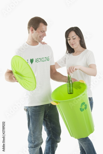 Couple throwing glass bottle in the recycling bin