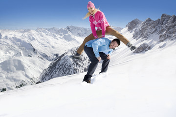 Laughing woman leap frogging over husband in snow