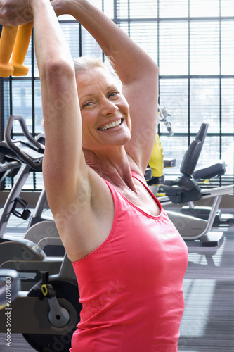 Active woman exercising with dumbbells in health club