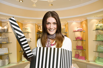 Excited woman opening hat box in expensive boutique