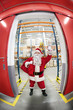 Santa Claus + gate to storehouse full of gifts in greeting pose