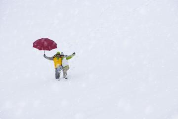 Couple walking through snow together holding umbrella