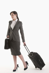 Young woman in suit with wheeled suitcase