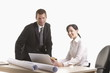 Man and woman with plans and laptop at desk