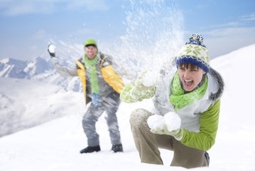Smiling couple having snowball fight in on mountain top together