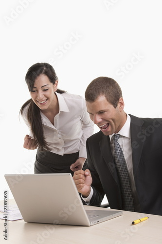 Man and woman at desk with laptop looking successful