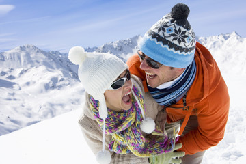 Smiling couple playing together in snow with mountain in background