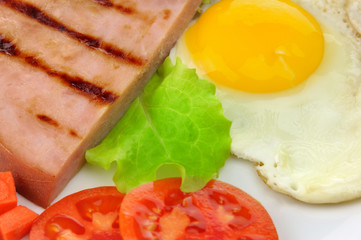 Sliced grilled ham with egg and vegetables close up