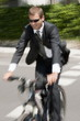 Businessman in suit riding bicycle to work