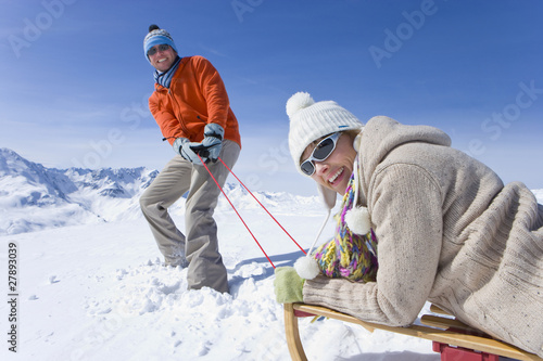 Man puling wife through snow on sled