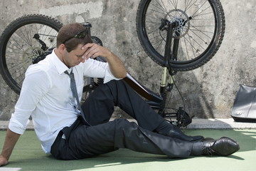 Businessman in suit next to broken bicycle