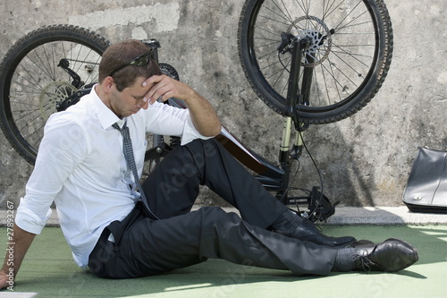 Businessman in suit next to broken bicycle