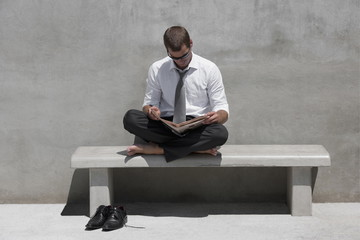 Barefoot businessman sitting on bench reading newspaper