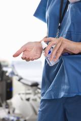 Nurse applying hand sanitizer in hospital