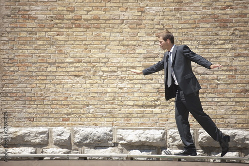 Man in suit walking on ramp by wall