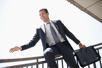 Businessman in suit sliding down bannister