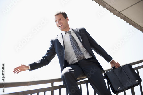 Businessman in suit sliding down bannister