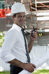 Man with hardhat, walky talky radio, and architectural plans at construction site