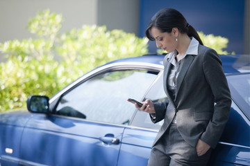 Woman in suit next to car looking at smartphone